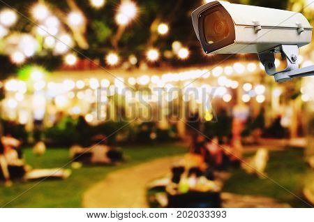 CCTV security indoor camera system operating with blurred image of abstract night light bokeh of night festival in garden background surveillance security technology concept