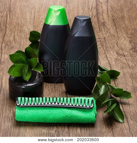 Natural hair care beauty products. Shampoo, hair conditioner, mask, comb and towel with green plant branches