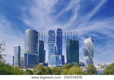 View on Moscow City business center skyscrapers office buildings, luxury apartments through green trees. Moscow city skyscrapers panorama. Modern european russian architecture. Sightseeing tour
