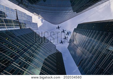 Vertical view on Moscow biggest business center Moscow City skyscrapers towers and flying jet planes aircraft with trails among skyscrapers office buildings. Plane in sky among skyscrapers