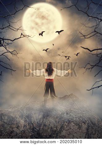Lord man standing on the rock looking on spooky dark sky. Halloween scene
