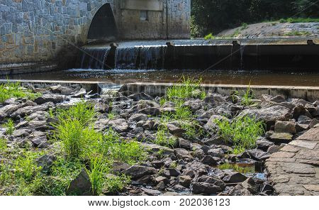 Small weir with grass and stone in front.