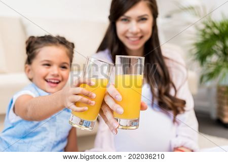 Little girl and her pregnant mother clink glasses with orange juice