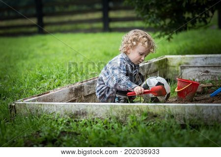 Young Caucasianboy With Curly Hair Playing In Sandbox