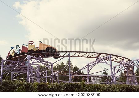 Roller Coaster Ride In Amusement Park At Evening, Low Key
