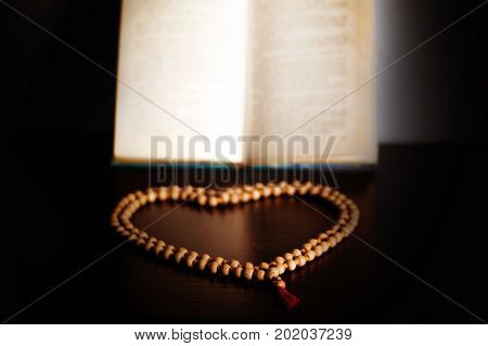 Wooden Rosary Clasped In The Shape Of A Heart Before The Prayer Book