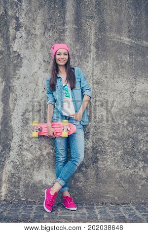 Youth Culture. Young Attractive Hipster Girl Stands With Skate Board On Concrete Wall`s Background,