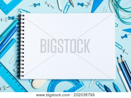 School supplies of blue and white colors on a blue background and notebook. Male or boyish still life on the topic of school study office work. Flat lay