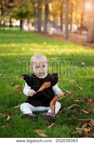 cute girl sits in the park in the autumn day
