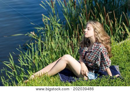 Relaxing young woman with long curly hair is sitting on the grass on the riverside. Rushy river bank as a background.