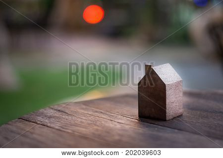 Wooden house model in garden with red bokeh background that seem like the sun.Wooden house model at sunset