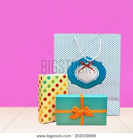 Gift box Trendy styled photo Two stylish gift boxes and gift package are standing on a lilac wall background Front view Modern pop art photo with space for text
