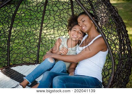 portrait of smiling african american mother hugging daughter while swinging on swing together in park