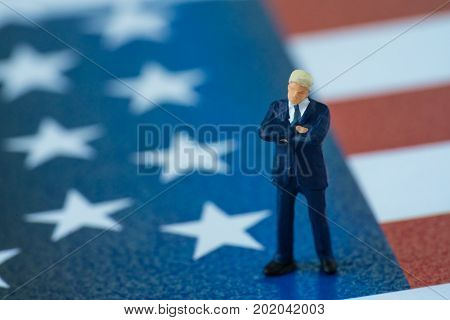miniature american businessman president standing on United State national flag.