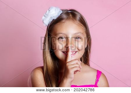 little girl with a secret . Kid keeping finger at her mouth as silence or secret sign