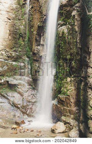 Waterfall in the mountains. Water falls from the mountain down to the rocks. It is photographed on an excerpt
