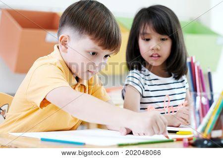 Boy drawing color pencils in kindergarten classroom preschool and kid education concept
