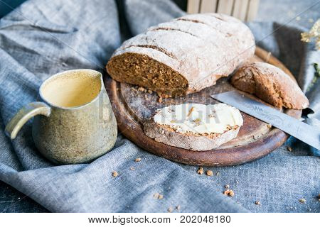 Close up rye bread with butter sandwich, knife and mug with coffee -- beautiful breakfast image on dark background