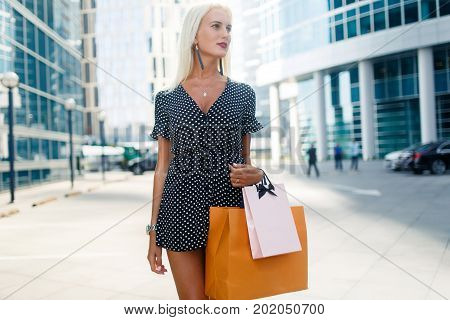 Photo of young model in dress with purchases on city street near modern buildings