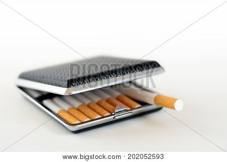 black and silver cigarette case with tobacco filter cigarettes background fades to white copy space selected focus very narrow depth of field