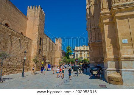 PALMA DE MALLORCA, SPAIN - AUGUST 18 2017: Unidentified people walking near of Cathedral of Santa Maria of Palma La Seu in a gorgeous blue sky, in Palma de Mallorca, Spain.