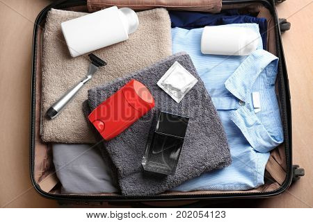 Suitcase with clothes, towels and different male hygiene items on floor