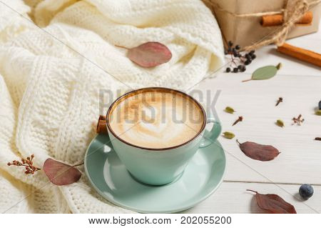 Autumn morning composition background. Blue coffee cup with hot foamy cappuccino, cloves, cinnamon and warm sweater at white wood. Fall spicy drinks concept, copy space