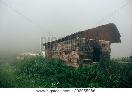 Old wooden abandoned house on green grass among dense fog, mist. Misterious dramatic view concept