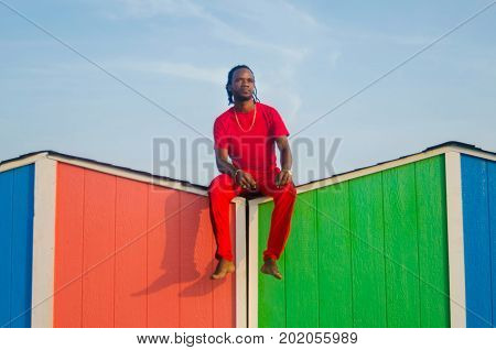Man Sitting On Top Of A Beach House