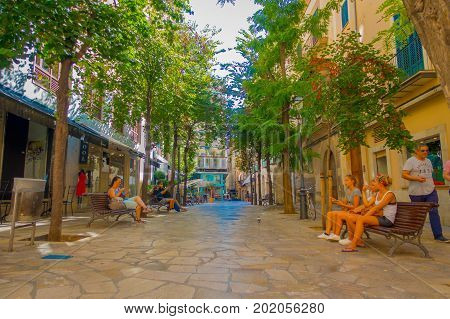 PALMA DE MALLORCA, SPAIN - AUGUST 18 2017: Unidentified people sitting in a public chairs while other turist keep walking throug at Boulevard Born in Palma de Mallorca, Spain, Europe.