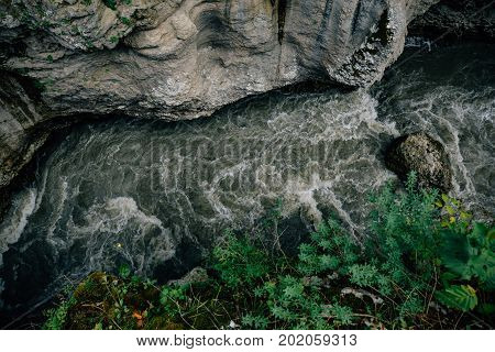 Narrow cleft in rocks, gorge, mountain river, top view, toned