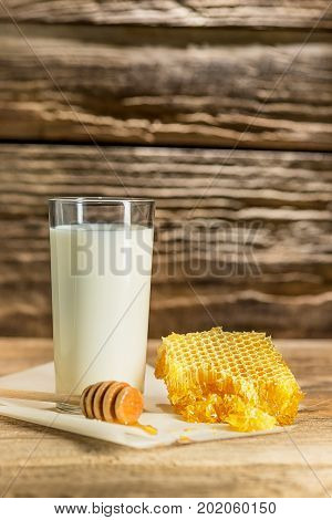 Sweet honeycomb and milk on wooden studio background