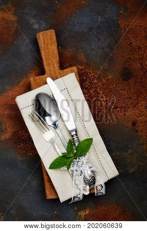 Vintage silverware and mint sprig on dark grunge table. Top view. Copy space for text. Toned image