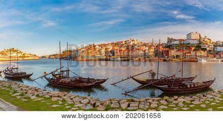 Panoramic view of traditional rabelo boats with barrels of Port wine on the Douro river, Ribeira on the background, Porto, Portugal.