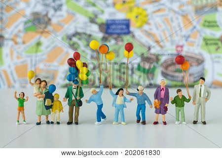 Miniature people with family holding balloons with map in the background as happy family or travel concept.