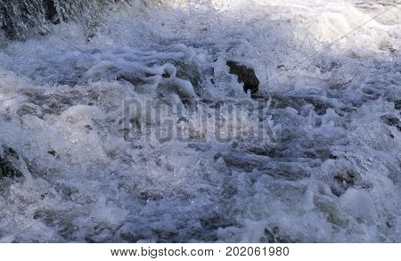 small waterfall at summer flowing water. background nature.