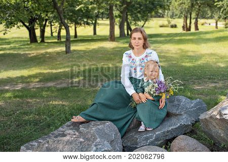 Family mom with daughter in vintage retro style linen dresses sitting on a stone rock in the park forest with bouquet of flowers smiling