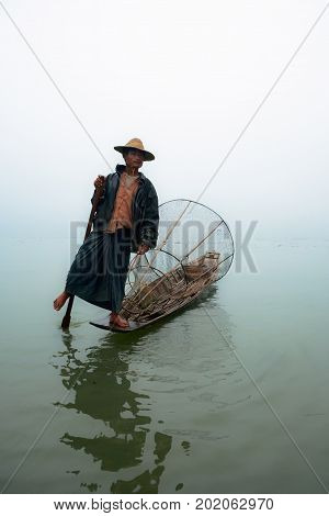 Inle Lake Myanmar - January 04 2007: Local fisher with traditional Burmese fishing net standing on stern of long boat and rowing oar by leg on Inle lake Myanmar.