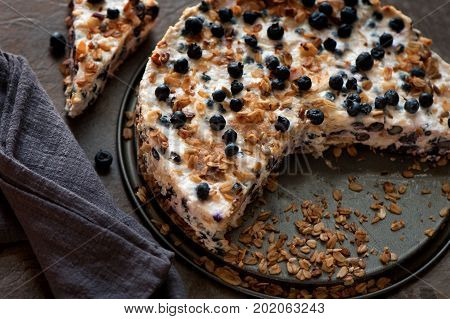 Sour cream cake with granola biscuits and blueberries. top view