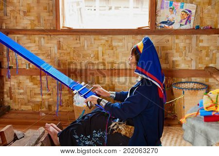 Inle Lake Myanmar - January 04 2007: Young woman of Kayan Lahwi (Padaung) people wearing brass coils on long neck weaving traditional Burmese handmade textile in village on Inle lake in Shan state.