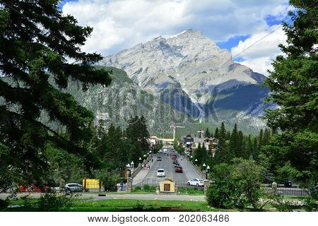 Banff Alberta Canada,June 25th 2015.Cars driving down main street in Banff Alberta with mount Norquay in the background.Come to Alberta and visit Banff.