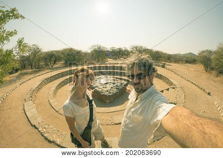 Couple of tourists at Hoba meteorite view point Namibia Africa. The meteorite is composed by high density heavy metals mostly iron and nickel with traces of cobalt.