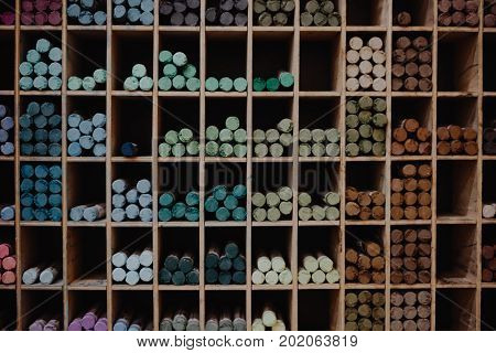 Multicoloured chalk on on the shelf on the store background concept