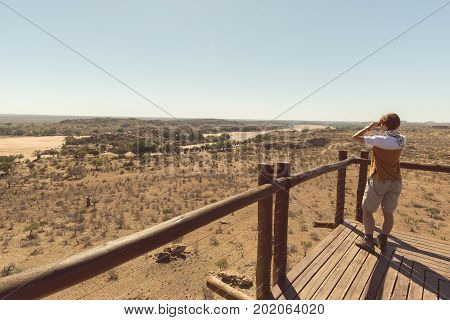 Tourist looking at panorama with binocular from viewpoint over the Mapungubwe National Park travel destination in South Africa.