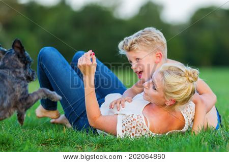Woman Romps With Her Son And A Dog On The Grass