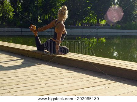 Young attractive woman doing yoga exercises in the park. Kapotasana