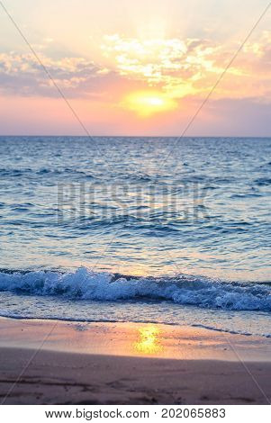 Sunset on the Sea of Azov with waves and a beach with fine sand for a background.