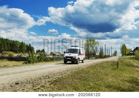 SVERDLOVSK OBLAST RUSSIA - MAY 20 2017: Ambulance car going on call through the village
