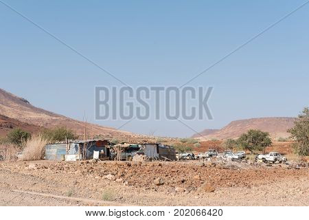 BERGSIG NAMIBIA - JUNE 28 2017: A street scene with shacks and car wrecks in Bergsig a small village in the Kunene Region of Namibia