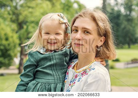 Portrait of Family mom with daughter in vintage retro style linen dresses with bouquet of flowers